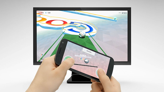 An image of a user's hands holding a mobile device with WWM on the screen, while there is a computer screen with WWM playing in the background.