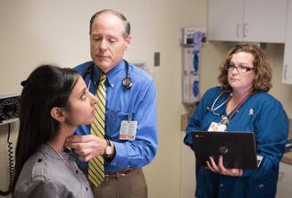 Arzt und Krankenschwester, die eine Patientin mithilfe eines Chrome-Geräts behandeln