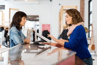 Karyawati penjualan membantu pelanggan dengan perangkat Chrome