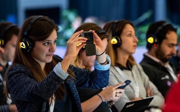 Mulher segurando smartphone para capturar um momento de uma palestra.