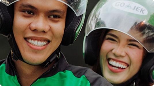 Foto en primer plano de 2personas riéndose que usan cascos de motocicleta con el logotipo de GO‑JEK.