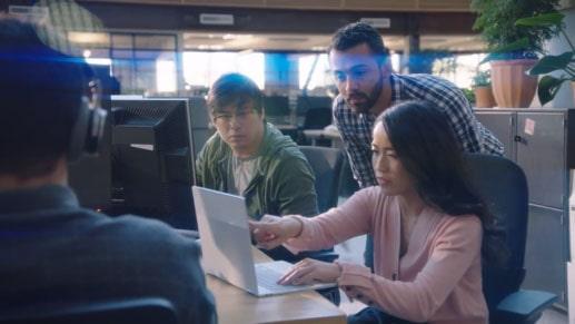 同僚 2 人がのぞき込む前で、パソコンの画面を指す女性の写真。