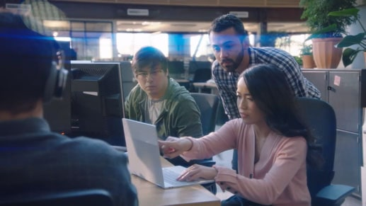 Shot of a woman pointing at the computer while her 2 coworkers look on.