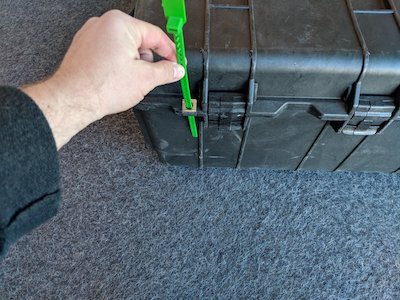 An image of a tamper-evident tag inserted through a silver ring on the ruggedized case on the TA100.